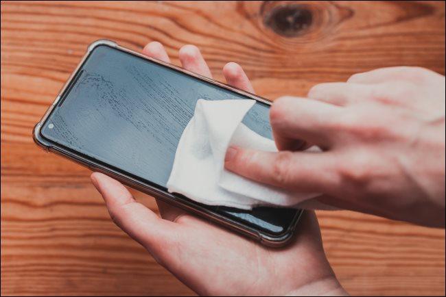 Osoba czyszcząca telefon chusteczką dezynfekującą.